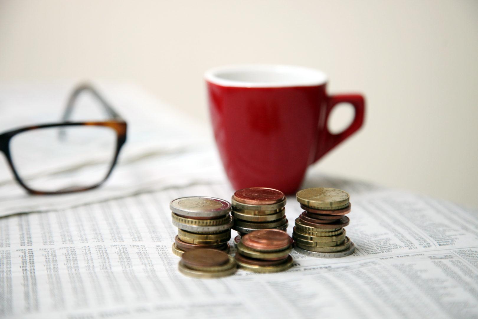 Das Bild zeigt aufgestapelte Münzen vor dem Hintergrund einer Kaffeetasse und einer Brille.
